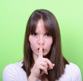 Retrato da menina com gesto para o silêncio contra o backgrou verde Fotos de Stock Royalty Free