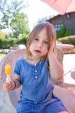 Retrato da menina com o lolly de gelo alaranjado no parque Fotos de Stock Royalty Free