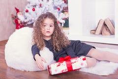 Retrato da menina consideravelmente doce perto de uma chaminé no Natal fotografia de stock royalty free