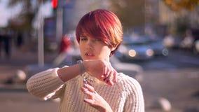 Retrato da menina cor-de-rosa-de cabelo bonita feliz que chama usando seu relógio no fundo borrado da rua filme