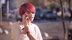 Retrato da menina cor-de-rosa-de cabelo bonita feliz que fala no telefone celular no fundo borrado da rua filme