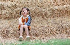 Retrato da menina da criança pequena e da roupa morna que sentam-se na pilha da palha em uma estação do inverno foto de stock royalty free