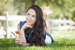 Retrato da menina da raça misturada que coloca na grama Foto de Stock