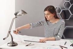 Retrato da menina de cabelo escuro nova do estudante com cabelo longo em camisa listrada que senta-se na tabela na casa, fazendo  imagem de stock royalty free
