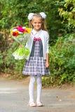 Retrato da menina de primeiro grau de sete anos com um ramalhete das flores Imagem de Stock