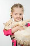 Retrato da menina de quatro anos alegre com um gato em seus braços Foto de Stock