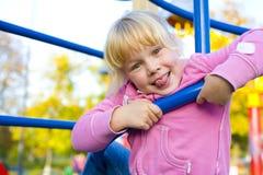 Retrato da menina de seis anos brincalhão no campo de jogos Fotografia de Stock Royalty Free