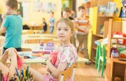 Retrato da menina de sorriso alegre que guarda um brinquedo colorido brilhante no jardim de infância - Moscou da boneca, Rússia - Imagens de Stock Royalty Free