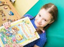 Retrato da menina de sorriso alegre que guarda um livro colorido brilhante no jardim de infância - Moscou, Rússia - 4 de fevereir Fotos de Stock