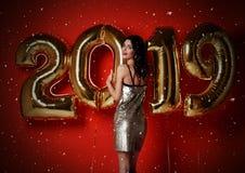 Retrato da menina de sorriso bonita em confetes de jogo do vestido dourado brilhante, tendo o divertimento com ouro 2019 balões n fotografia de stock royalty free