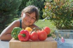 Retrato da menina de sorriso bronzeada com legumes frescos dentro imagens de stock royalty free