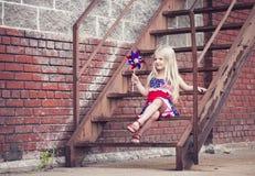 Retrato da menina de sorriso com o girândola que senta-se em escadas imagens de stock