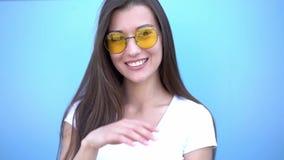 Retrato da menina de sorriso do moderno da forma da beleza nos óculos de sol no fundo azul vídeos de arquivo