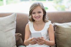Retrato da menina de sorriso que senta-se no sofá usando o telefone celular na sala de visitas Imagens de Stock