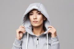 Retrato da menina desportivo brutal na capa e no sportswear que olham a câmera sobre o fundo branco imagem de stock