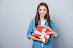 Retrato da menina do feliz aniversario novo, guardando um presente no vermelho fotografia de stock