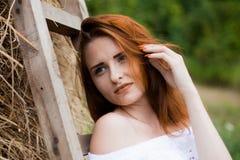Retrato da menina do ruivo no campo perto do monte de feno Fotos de Stock Royalty Free