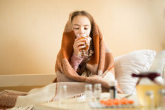 Retrato da menina doente coberto na cobertura que bebe o chá quente fotografia de stock