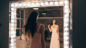 Retrato da menina elegante no vestido de noite que levanta na frente de um espelho com as luzes no vestuário Morena com filme