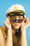 Retrato da menina em vidros escuros e em um pico-tampão do mar Imagem de Stock Royalty Free