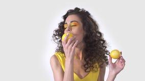 Retrato da menina encaracolado bonito nova que morde um limão fresco ácido grande com prazer e que guarda outro na outra mão video estoque