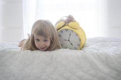 Retrato da menina engraçada com o despertador enorme sobre o fundo branco Fotos de Stock