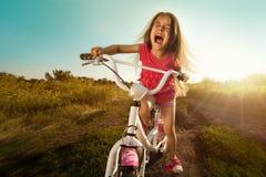 Retrato da menina engraçada feliz na bicicleta imagem de stock royalty free