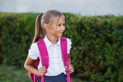Retrato da menina da escola com a trouxa após a escola Começo das lições Primeiro dia da queda imagem de stock royalty free