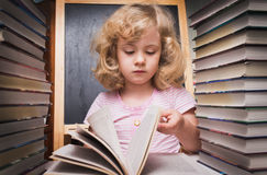 Retrato da menina esperta bonito que lê um livro Foto de Stock