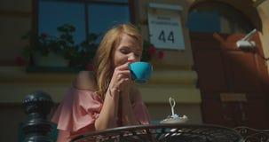Retrato da menina feliz bonita com café bebendo do cabelo louro e da composição natural e apreciação do dia ensolarado no vídeos de arquivo