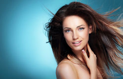 Retrato da menina feliz com cabelo de sopro escuro longo contra o azul imagem de stock