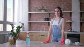 Retrato da menina feliz da empregada nas luvas de borracha durante a limpeza geral de deveres da culinária e do agregado familiar video estoque
