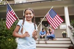Retrato da menina fora da casa familiar que guarda bandeiras americanas fotografia de stock