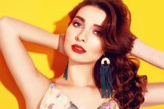 Retrato da menina da forma no levantamento amarelo do fundo A menina moreno bonita com por muito tempo cerly cabelo e o rosa comp imagens de stock royalty free