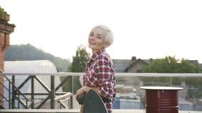 Retrato da menina loura atrativa do moderno com um skate que levanta à câmera e que sorri no ar livre cute filme