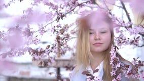 Retrato da menina loura bonita que levanta em ramos de ?rvore de floresc?ncia com flores cor-de-rosa Esta??o de mola video estoque