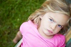 Retrato da menina loura da criança com os olhos azuis que olham a câmera que relaxa em uma rede colorida Fotos de Stock Royalty Free
