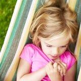 Retrato da menina loura da criança com os olhos azuis que olham a câmera que relaxa em uma rede colorida Fotografia de Stock Royalty Free