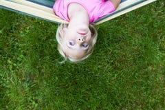 Retrato da menina loura da criança com os olhos azuis que olham a câmera que relaxa em uma rede colorida Fotografia de Stock