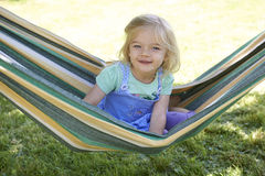 Retrato da menina loura da criança com os olhos azuis que olham a câmera que relaxa em uma rede colorida Imagens de Stock