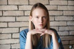 Retrato da menina loura nova com fones de ouvido Restos principais da menina em suas mãos da cabine Fotos de Stock