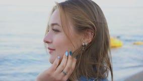 Retrato da menina macia que levanta na câmera, no sorriso bonito e nos suportes contra o mar e o céu azuis no por do sol no verão vídeos de arquivo