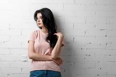 Retrato da menina moreno bonita esperta nos monóculos com a composição natural que está perto da parede de tijolo branca Imagens de Stock Royalty Free