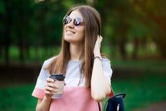 Retrato da menina moreno bonita nos ?culos de sol que anda abaixo da rua Mantendo a bebida afastada ? disposi??o Sorriso imagem de stock royalty free