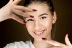 Retrato da menina moreno bonita nova com a composi??o natural que guarda seus dedos na frente de sua cara fotos de stock