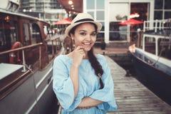 Retrato da menina moreno caucasiano branca de sorriso bonita no cais do cais do iate do barco, no chapéu azul do vestido e de pal fotografia de stock