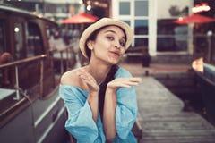 Retrato da menina moreno caucasiano branca de sorriso bonita no cais do cais do iate do barco, no chapéu azul do vestido e de pal fotografia de stock royalty free
