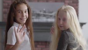 Retrato da menina moreno e da menina do albino com as mãos de ondulação do cabelo longo que olham o sorriso da câmera Conceito de vídeos de arquivo