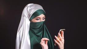 Retrato da menina muçulmana árabe bonita que usa o telefone celular filme