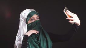 Retrato da menina muçulmana árabe bonita que usa o telefone celular video estoque